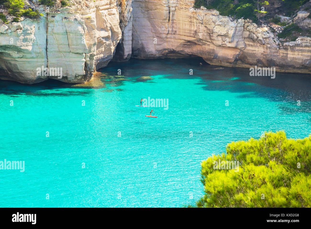 Menschen paddleboarding auf dem smaragdgrünen Wasser von Cala Mitjana, Menorca, Balearen, Spanien Stockbild