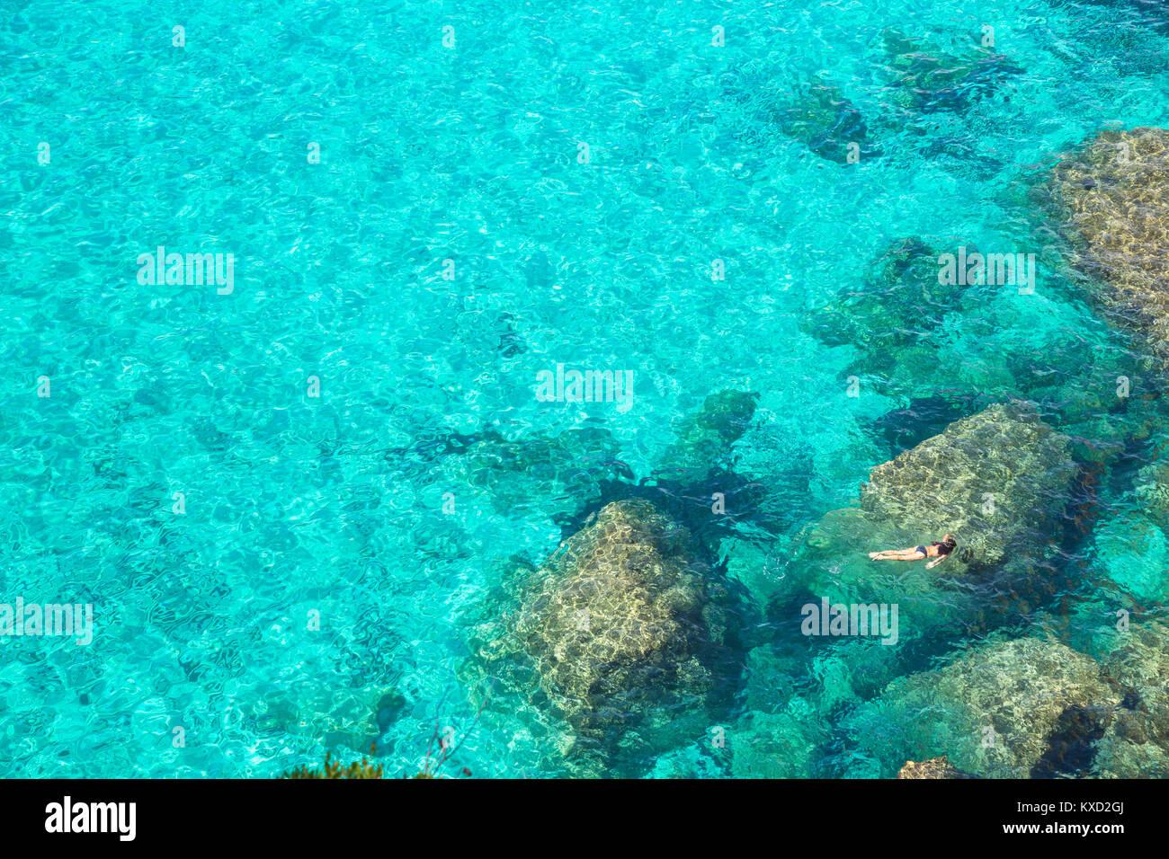 Person schwimmen im smaragdgrünen Wasser von Cala Mitjana, Menorca, Balearen, Spanien, Europa Stockbild