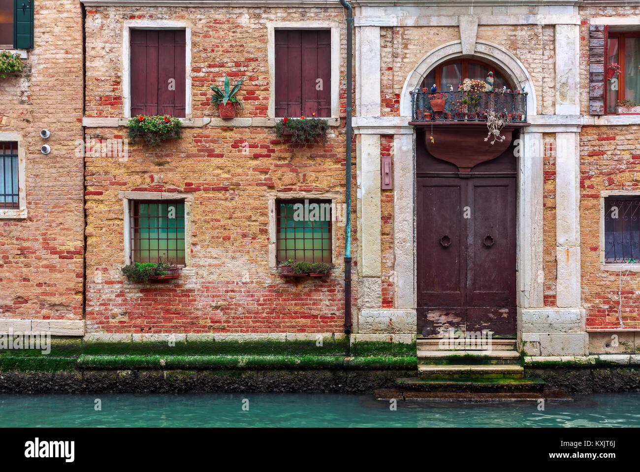 Fassade des teilweise bemoosten alten Backsteinhaus mit Holz vintage Tür auf schmalen Kanal in Venedig, Italien. Stockbild