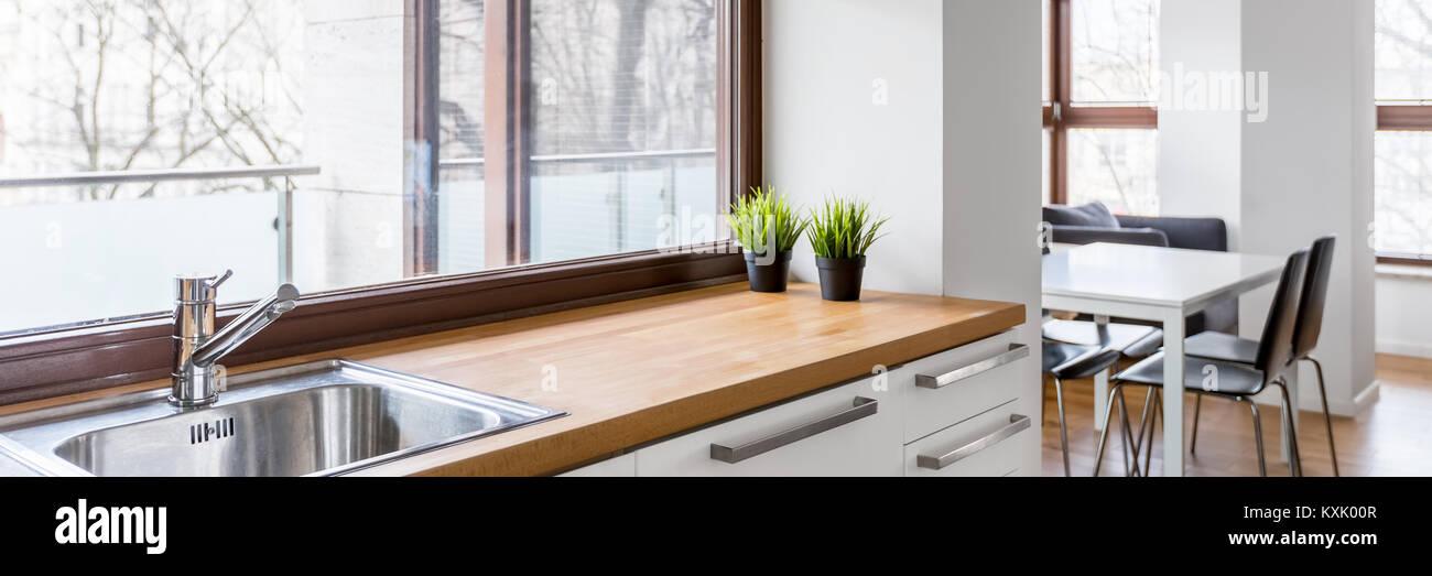 Weiße Küche mit Holz- Arbeitsplatte, silber Waschbecken und große ...
