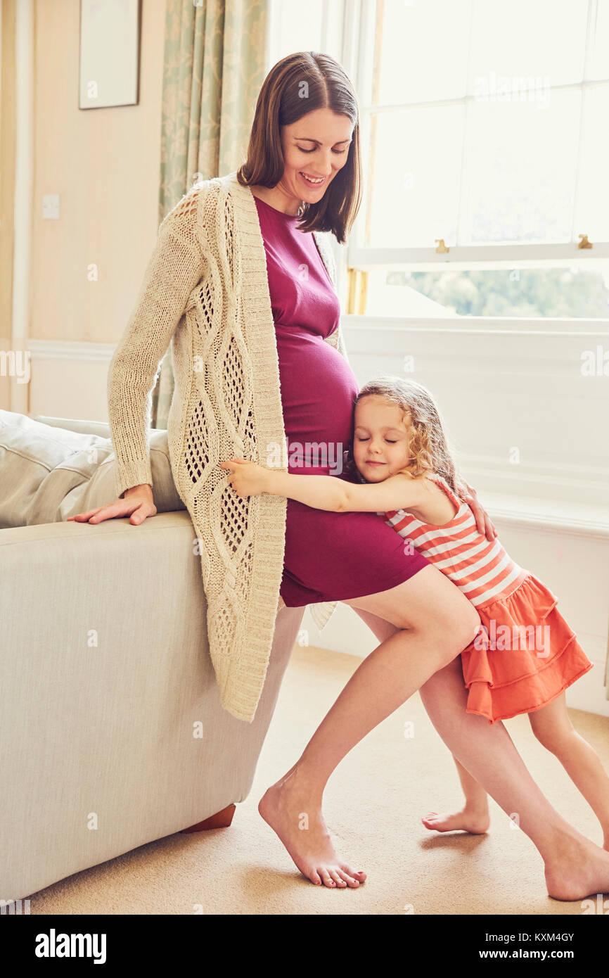 Mädchen hören zu und umarmen die schwangere Mutter Magen Stockbild