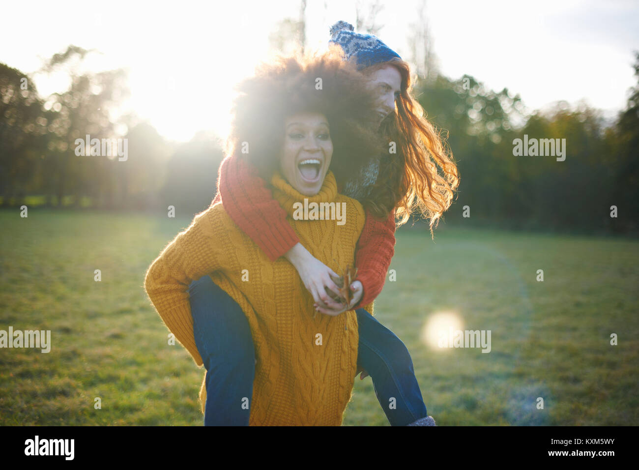 Zwei junge Frauen, die in der ländlichen Umgebung, junge Frau, Freund piggyback Ride Stockbild