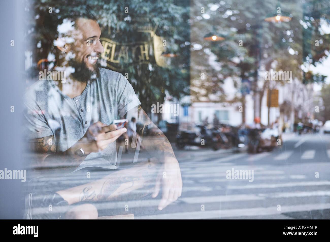 Junge männliche Hipster im Cafe Fensterplatz holding Smartphone, Shanghai French Concession, Shanghai, China Stockbild