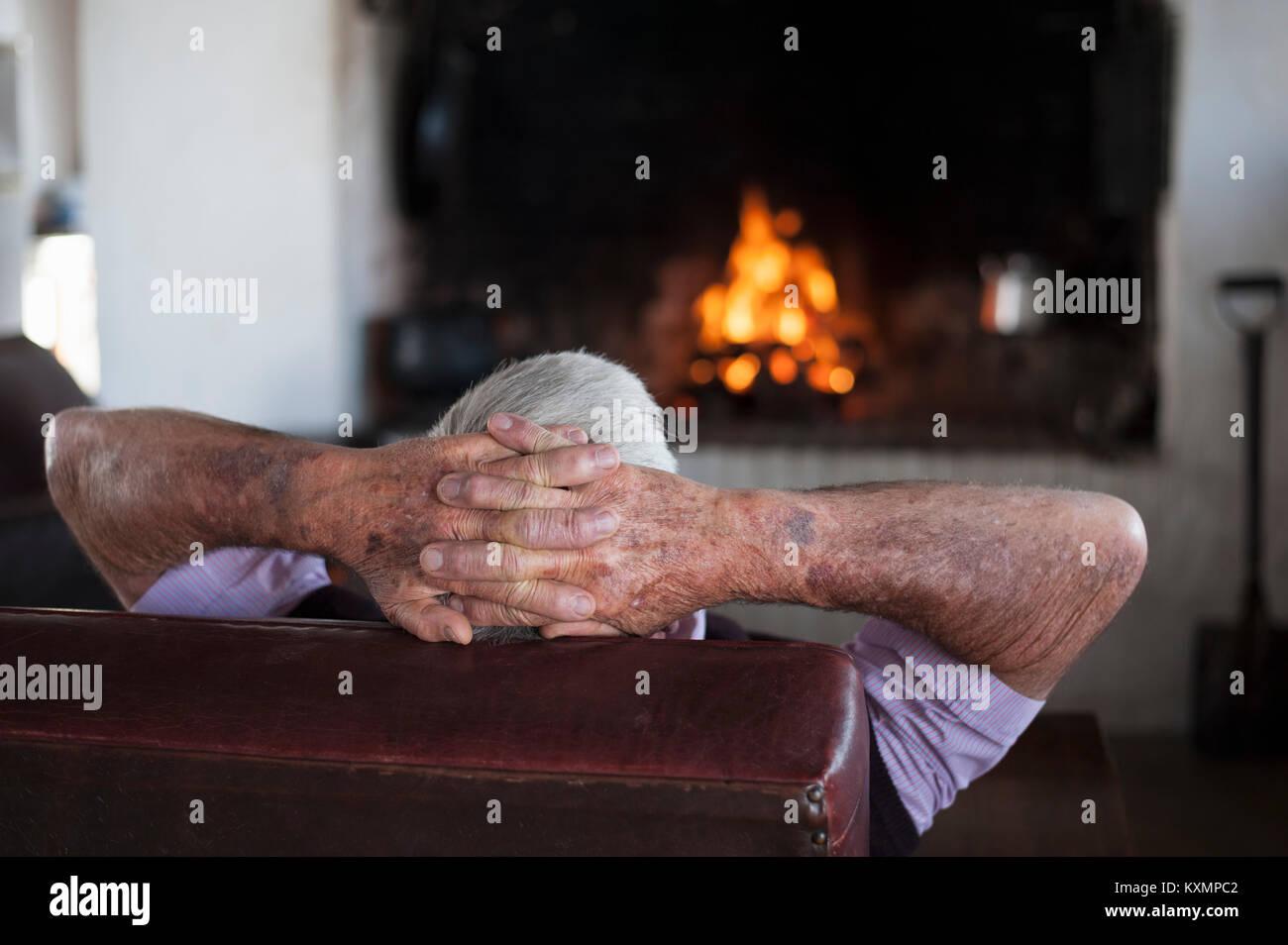 Ansicht der Rückseite des älteren Menschen zu Hause mit den Händen hinter seinem Kopf vor Kaminfeuer Stockbild