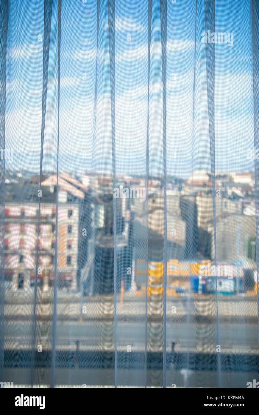 Ein Schuss durch ein Fenster mit einem Vorhang mit Blick über einen Teil der Stadt Genf Stockbild