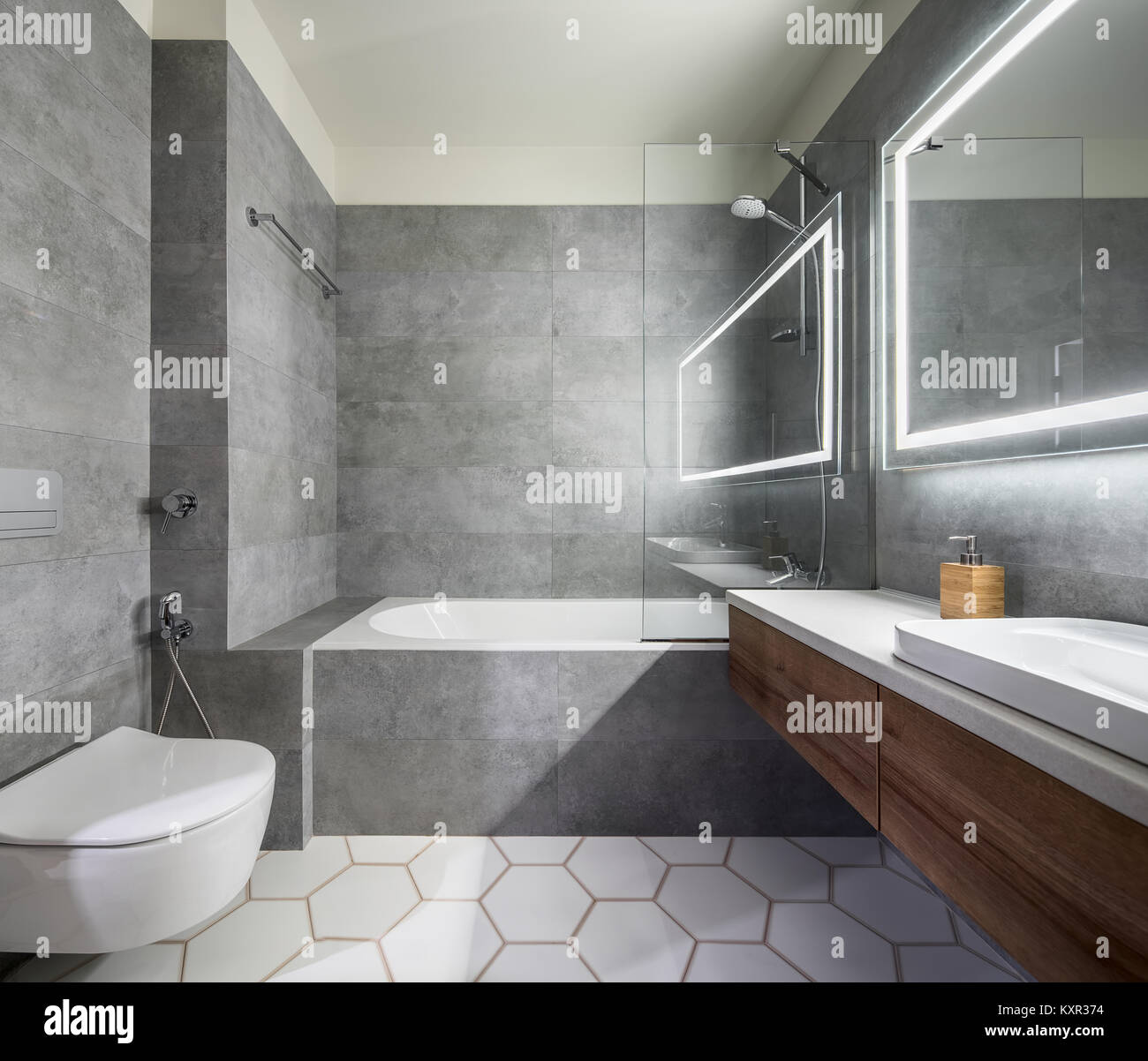 Modernes Badezimmer mit grauen und weißen Fliesen. Es gibt ...