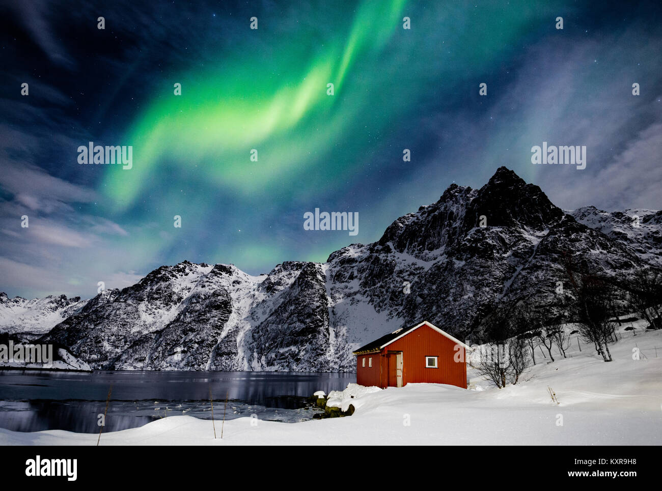 Lofoten Svolvaer, Aurora Borealis über einen zugefrorenen See und roten Rorbu, Norwegen. Stockbild