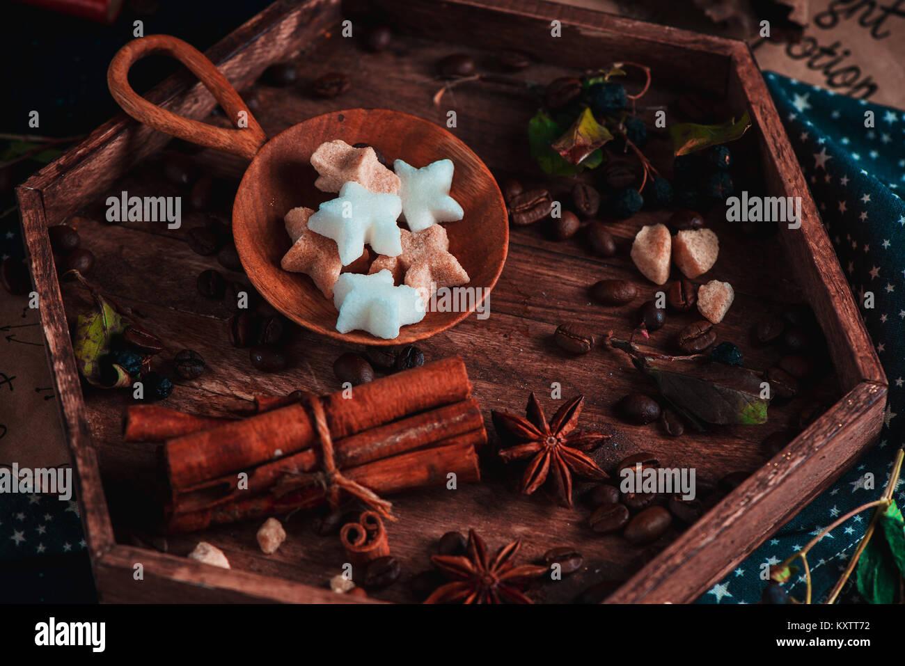 Holzplatte mit sternförmigen Zucker in einem Fach mit Gewürzen auf einem dunklen Hintergrund. Dunkle essen Fotografie Stockfoto