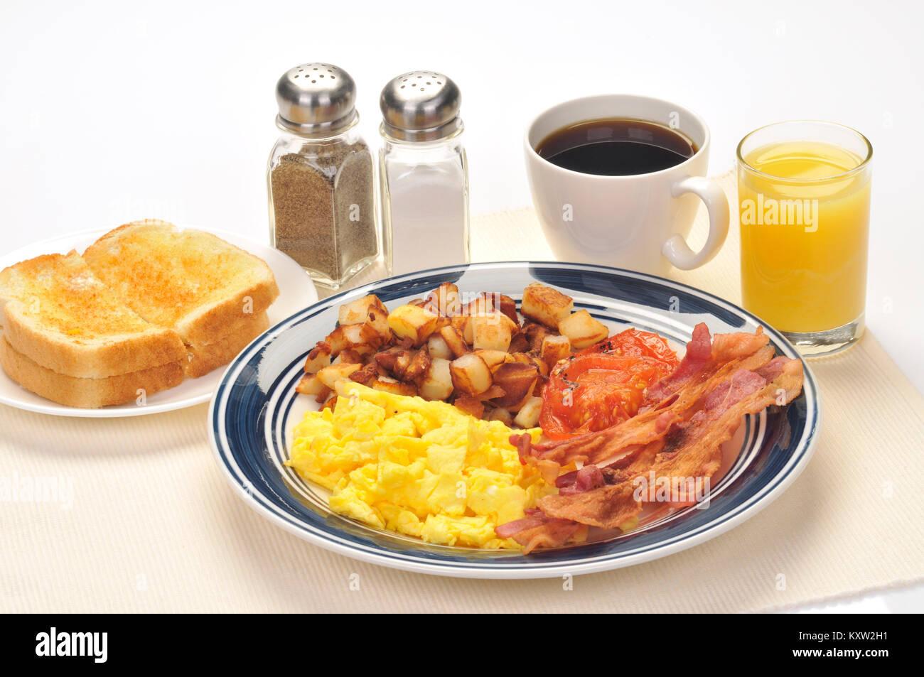 American blue Platte Frühstück mit Rührei, Hash Brown Kartoffeln, Speck, gegrillte Tomaten, Gebutterte Stockbild
