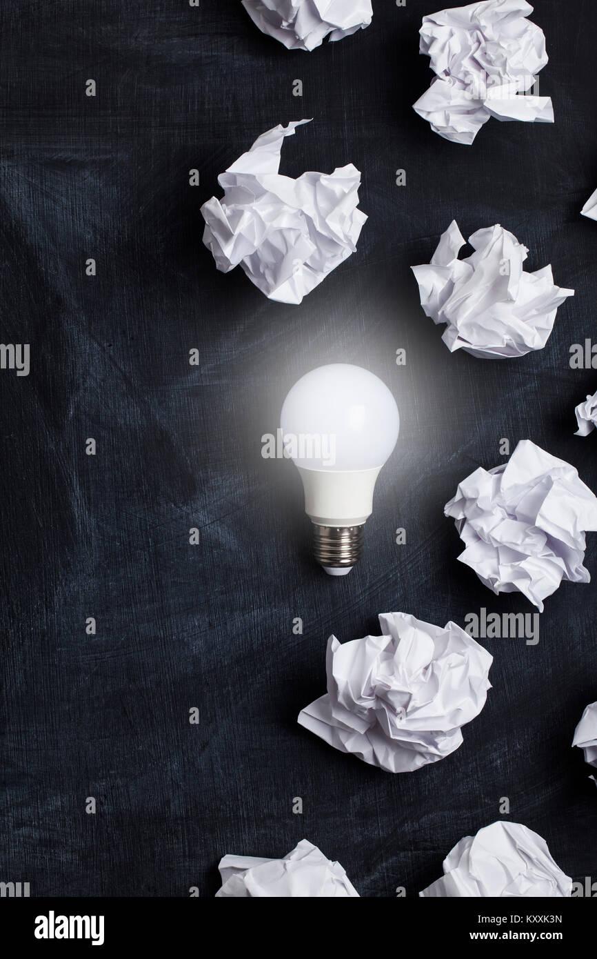 Inspiration und Phantasie Konzept. Glühbirne mit weißen zerknittertes Papier Dokumente Stockbild
