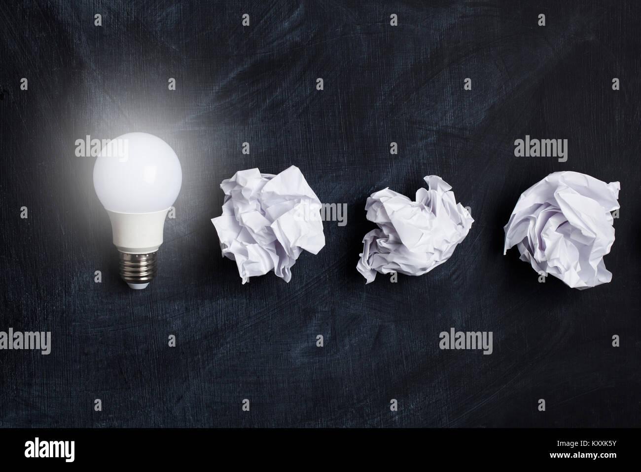 Inspiration und Phantasie Konzept. Glühbirne mit weißen zerknittertes Papier Dokumente Stockfoto