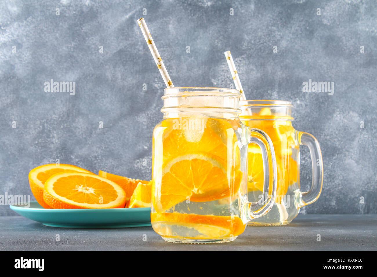 Orange detox Wasser in Maurergläser auf grauem Beton Hintergrund ...