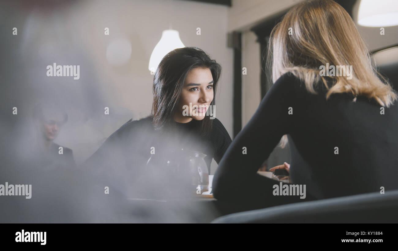 Schwarzhaarige junge Frau mit schwarzen Haaren Kaffee trinken und reden mit Freundin im Cafe Stockbild