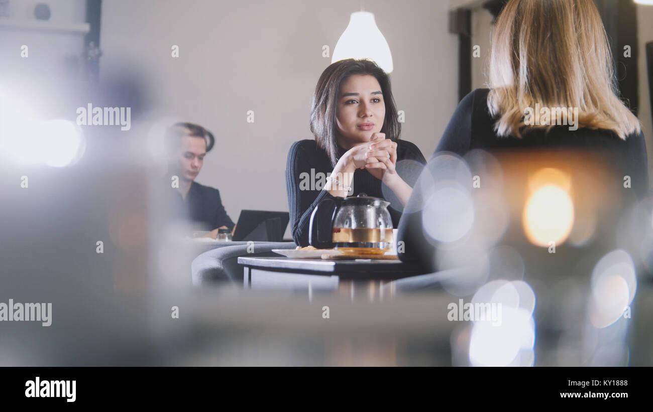 Hübsche, junge Frau mit schwarzen Haaren im Gespräch mit Freundin im Cafe Stockbild