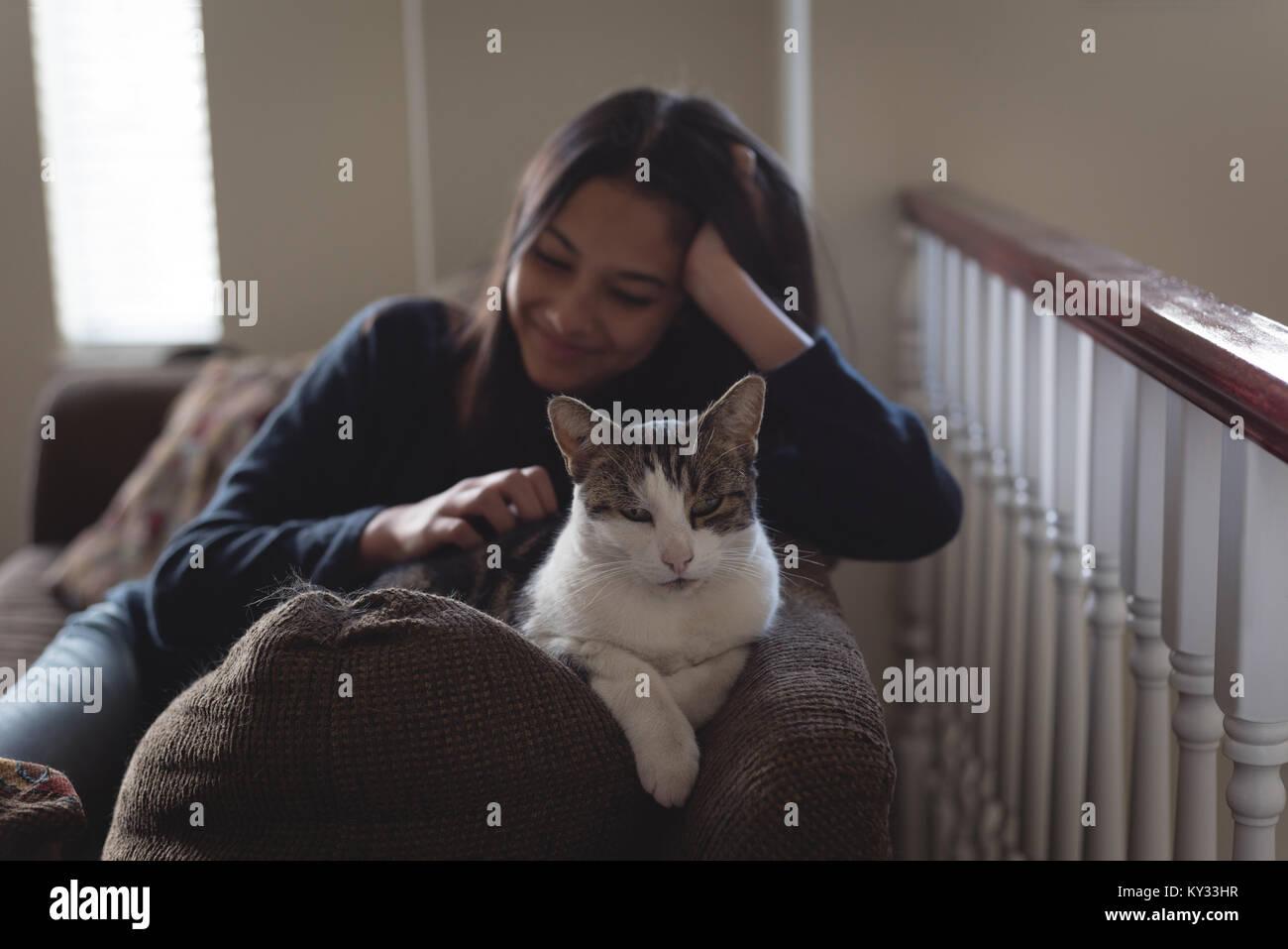 Junges Mädchen mit Katze auf Sofa im Wohnzimmer Stockbild