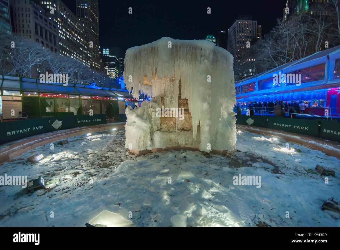 Besucher Bryant Park in New York Halt am Josephine Shaw Lowell Memorial Fountain, ein kaltes Wetter Eis hat Skulptur am Dienstag, 2. Januar 2018. Die Stadt hat eine Wetter beratenden Da zwischen 1 und 3 Zoll Schnee wird am Donnerstag vorhergesagt, von bitter kalt 1-Ziffern über das Wochenende folgt. (© Richard B. Levine) Stockfoto