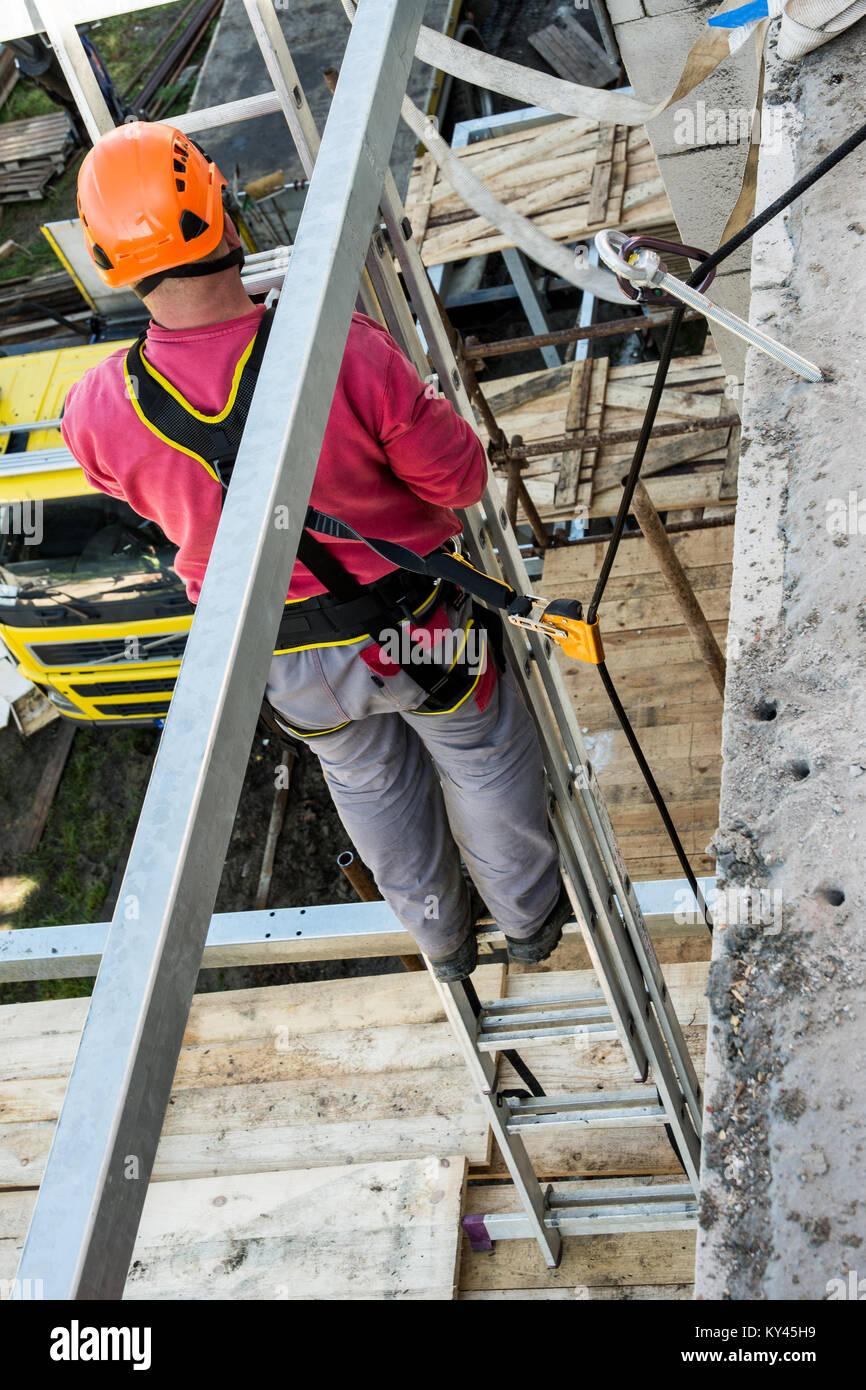 Höhe arbeitet auf dem Aufbau und der Sicherheit. Sichern des Arbeiters während der Arbeit auf einem Gerüst. Stockbild