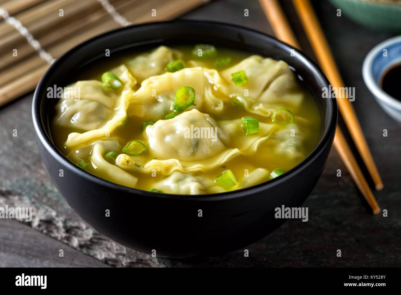 Eine Schüssel köstliche chinesische Wan-Tan-Suppe mit Frühlingszwiebeln garnieren. Stockbild