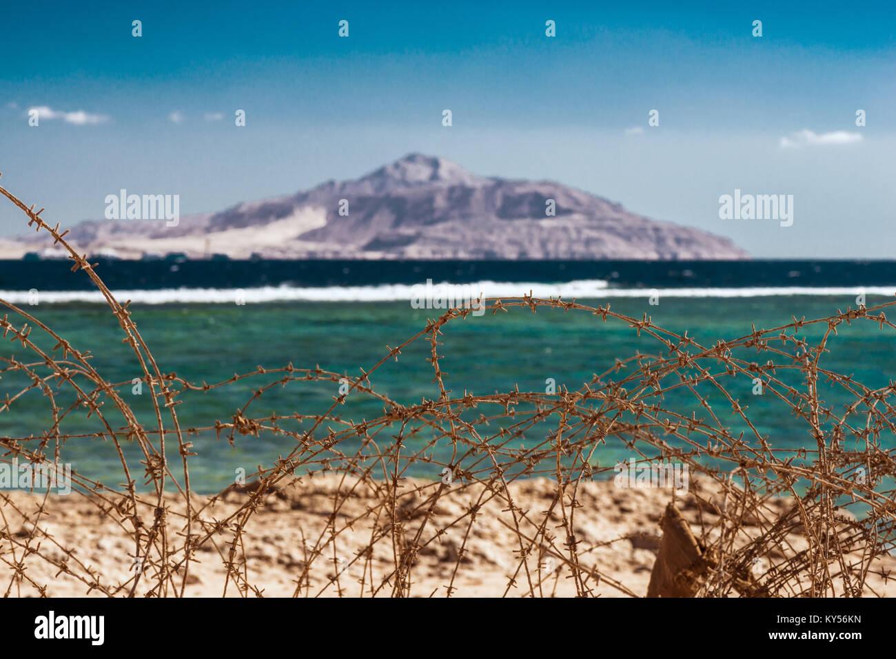 Alten Stacheldraht vor das Rote Meer und die Insel Tiran. . Kabel und blauem Himmel mit Wolken. Schutzzaun von Stacheldraht Stockbild