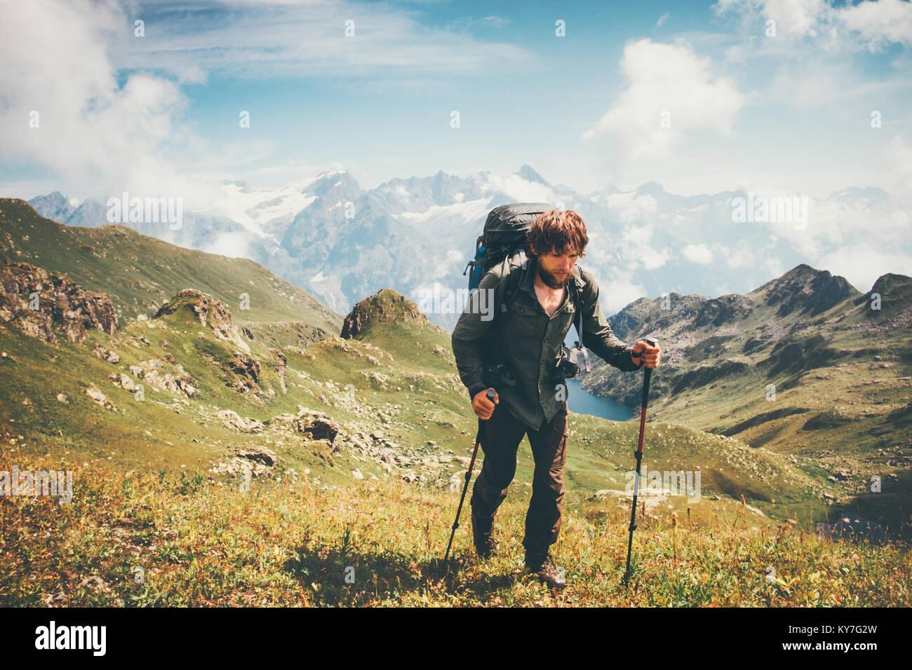 Man Bergsteigen mit Rucksack Reisen Lifestyle Konzept Abenteuer Sommer Ferien im Freien Bergen auf Hintergrund Bereich Stockbild