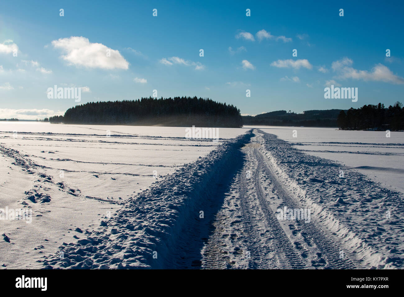 Eine schmale Straße in Schnee über einem See in Schweden Stockbild