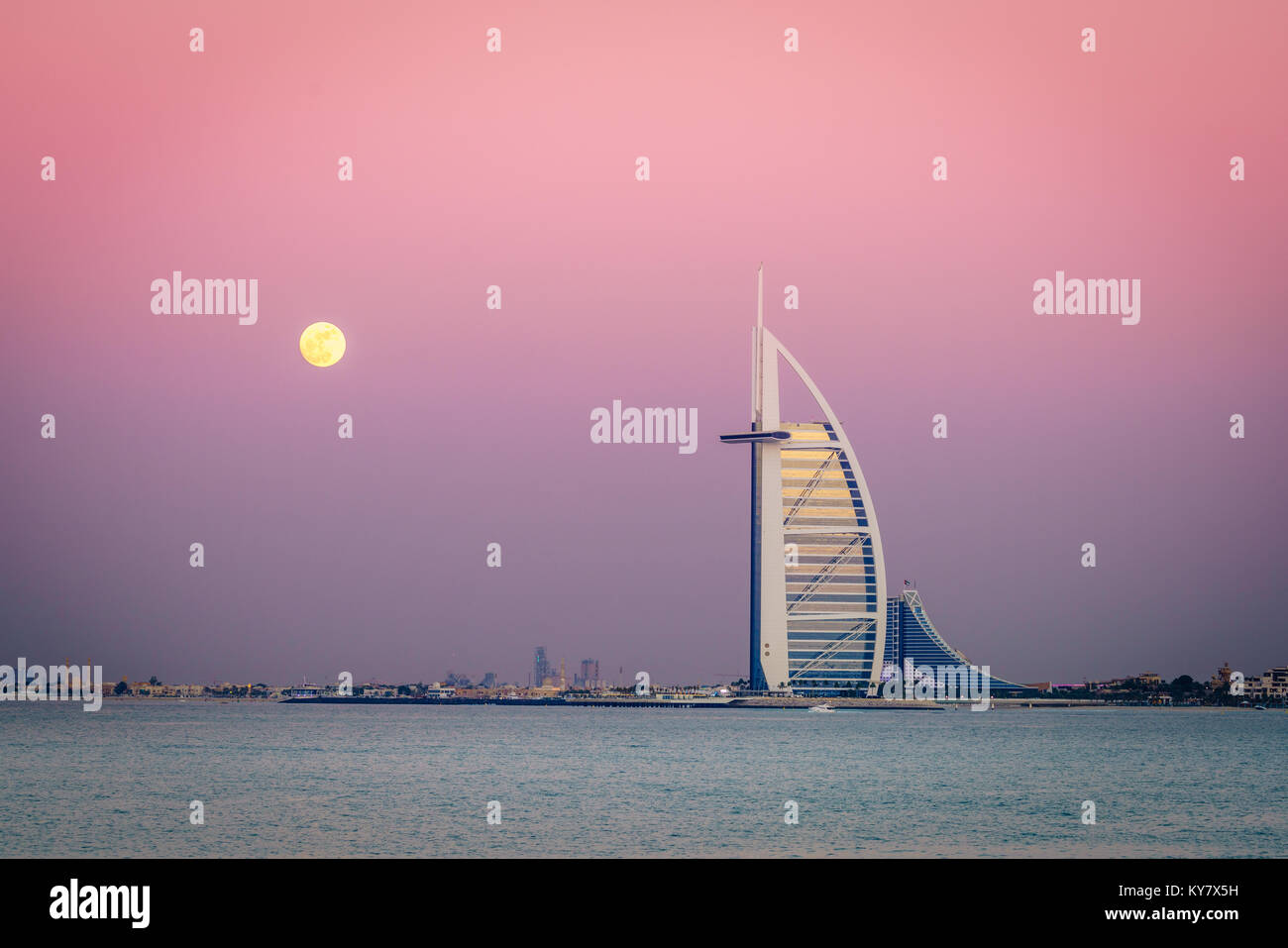 Dubai, VAE, 13. Dezember 2016: Vollmond steigt über das Burj Al Arab - das weltweit einzige 7-Sterne Hotel Stockbild