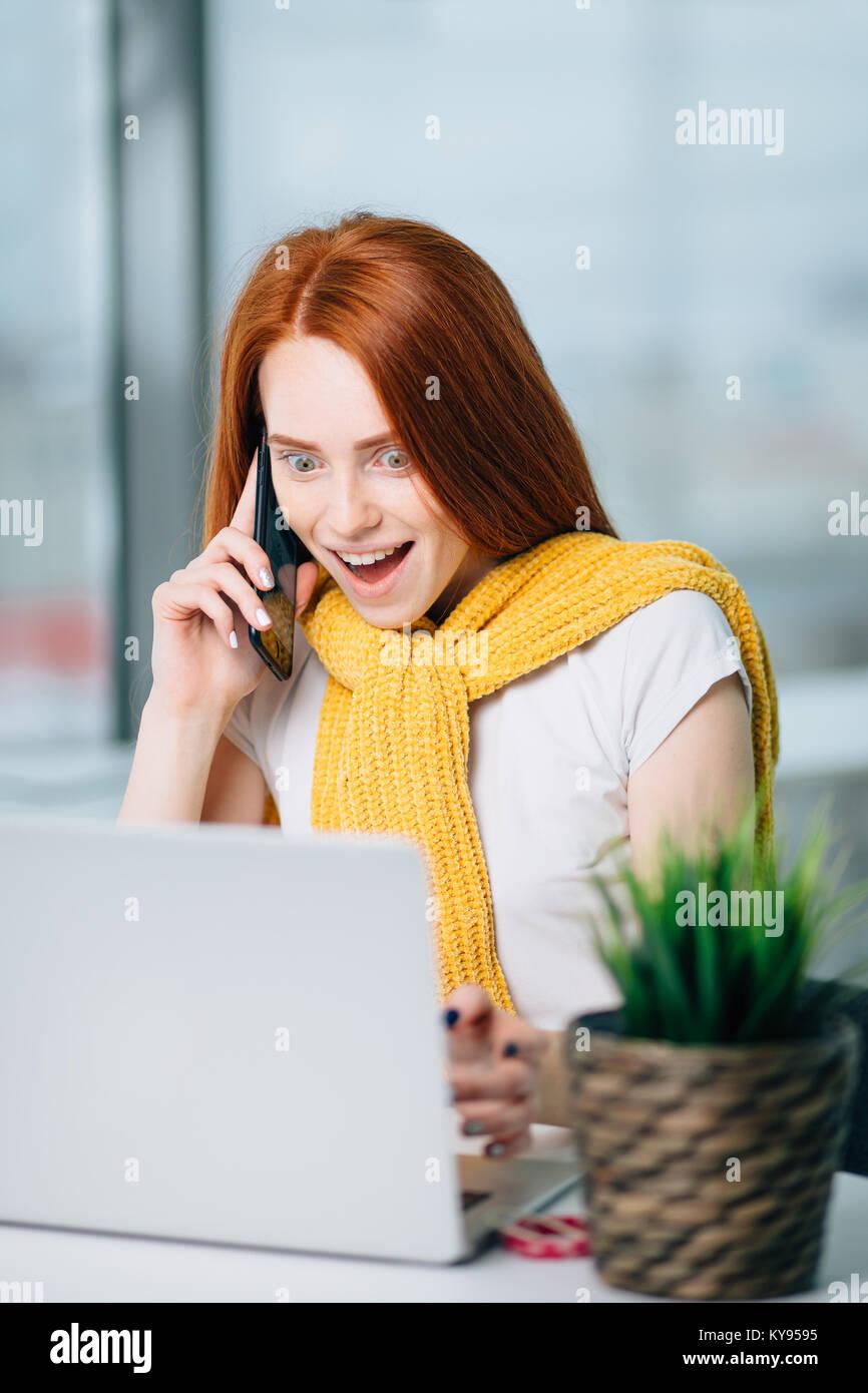 Überrascht junge brünette Frau allein mit Laptop und Mobiltelefon im Sommer Cafe Stockbild