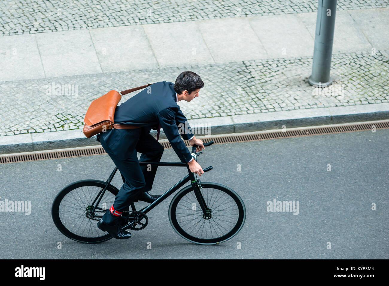 Junger Mann mit Anzug beim Reiten ein Fahrrad Stockbild