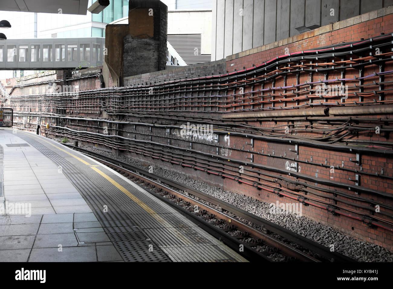 Leere Plattform und die Bahn auf der Schiene mit Infrastruktur Leitungen sichtbar auf der Mauer am Bahnhof in London Stockbild