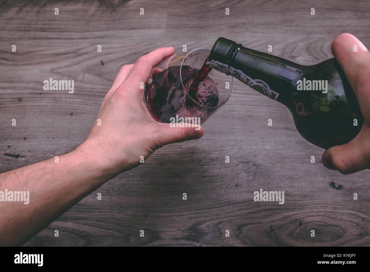 Blick von oben auf eine Hand mit einem Rotwein Flasche und gießt es in ein Glas Stockbild
