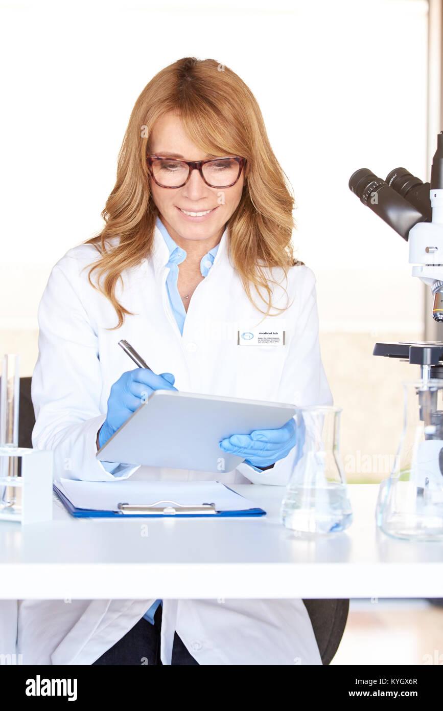Ein Lächeln im mittleren Alter Forscher Aufnahme ihre Ergebnisse auf einem Tablet im Labor. Stockbild