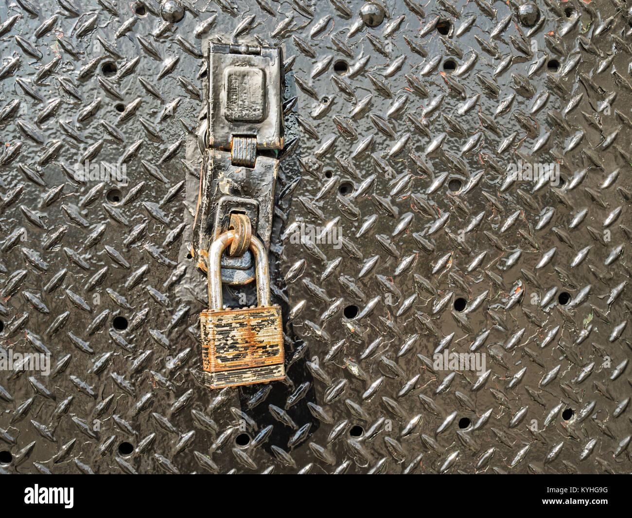 Alte rostige Bügeleisen Vorhängeschloss auf Metall Tür als Symbol der Sicherheit Schutz, sichere Stockbild