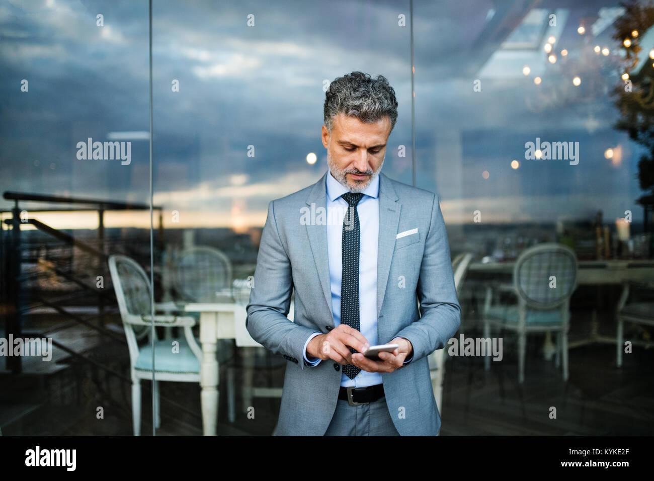 Geschäftsmann mit Smartphone in einen Außenpool Hotel Cafe. Stockfoto