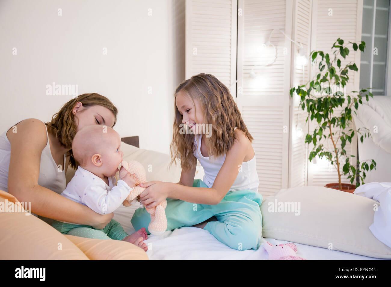 Drei Schwestern spielen Kinder am Morgen im Schlafzimmer Stockfoto