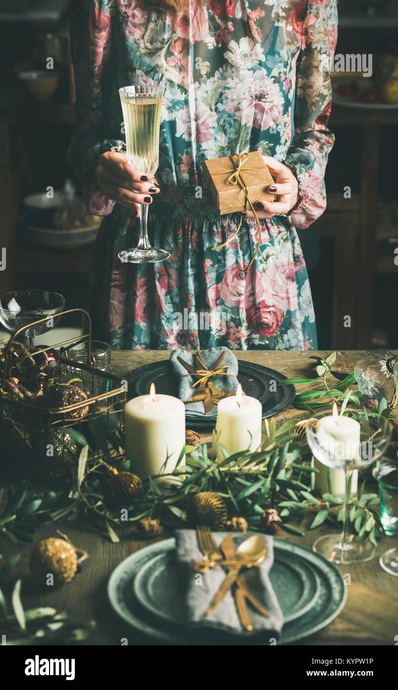 Frau in festliches Kleid holding Glas Champagner und ein Geschenk in ihren Händen im Holiday dekorierten Tisch Stockbild