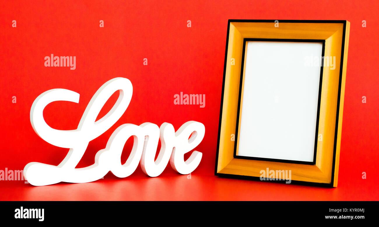 Weiß Liebe zeichen Kursiv mit einem leeren Bilderrahmen auf rotem ...
