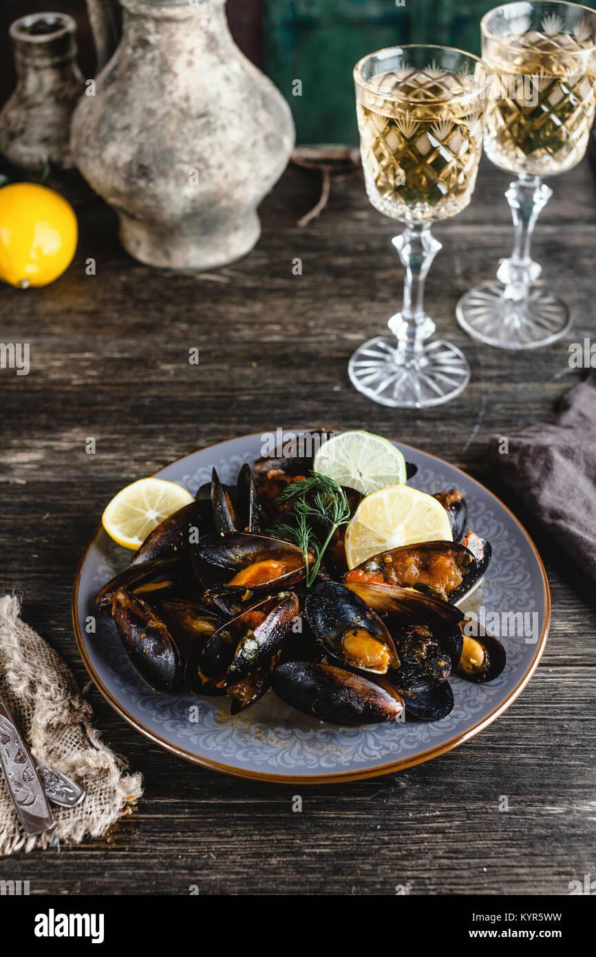 Gekochte Miesmuscheln mit Muscheln auf Platte mit zwei Gläser Weißwein auf hölzernen Tisch serviert Stockfoto