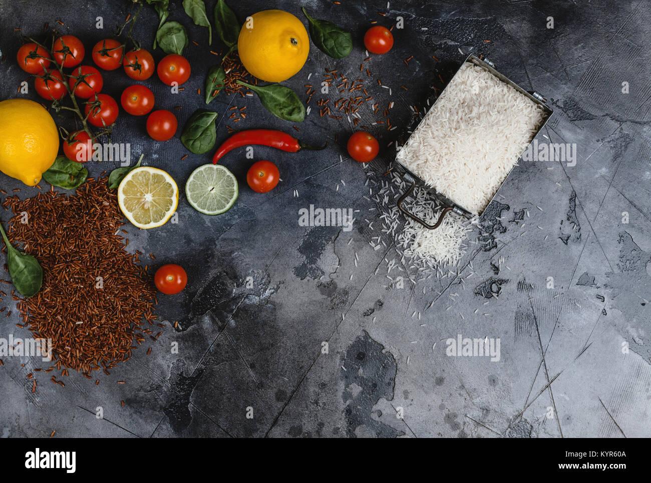 Blick von oben auf die rohen Reis im Container, Gewürze und Gemüse auf Zerkratzt graue Oberfläche Stockbild