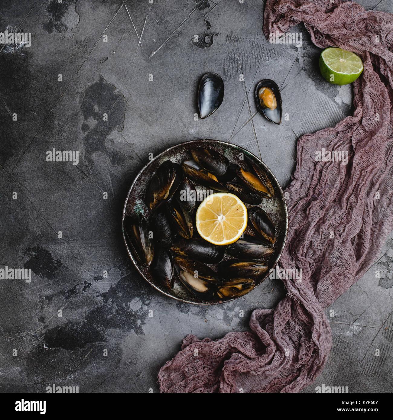 Blick von oben auf die leckeren Muscheln mit Muscheln auf vintage Platte und Kalk mit Zitrone und Tuch auf Grau Stockbild