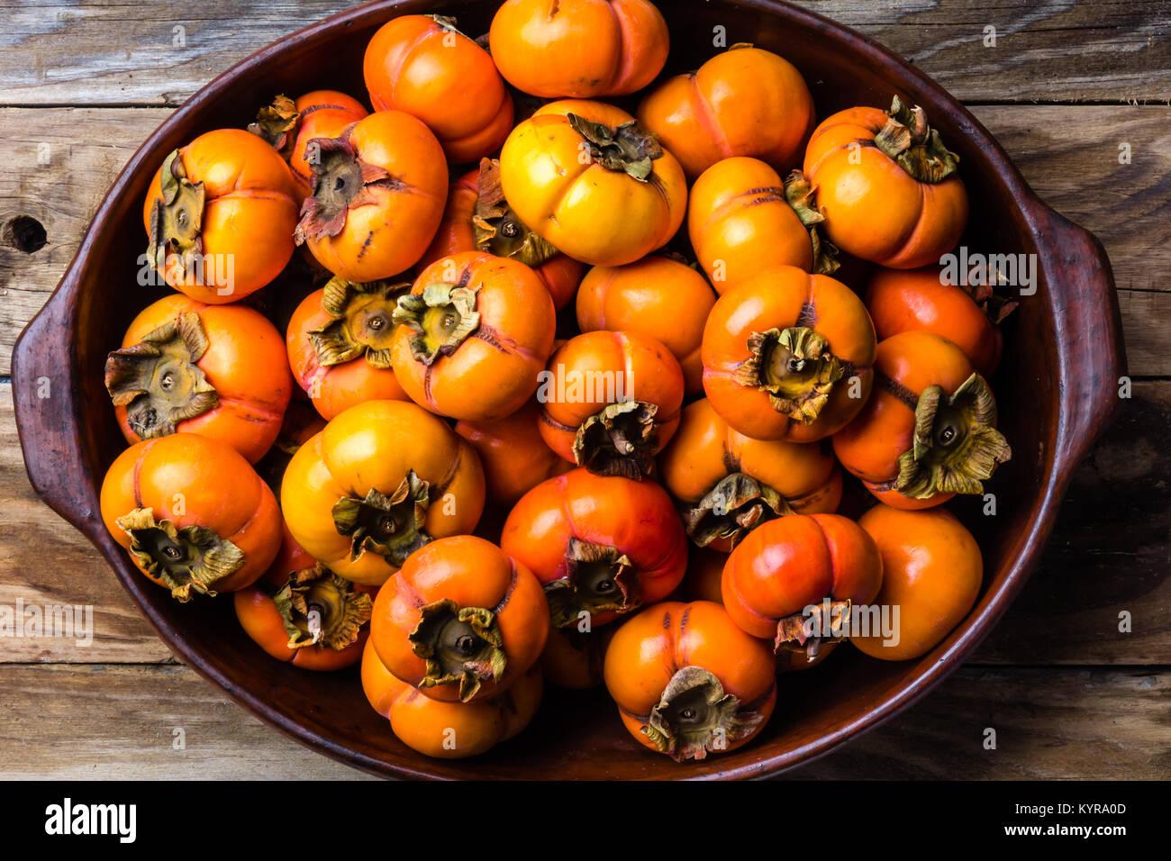 Topf mit frischen Früchten Persimone kaki auf alten Holz- Hintergrund. Platz kopieren Stockbild
