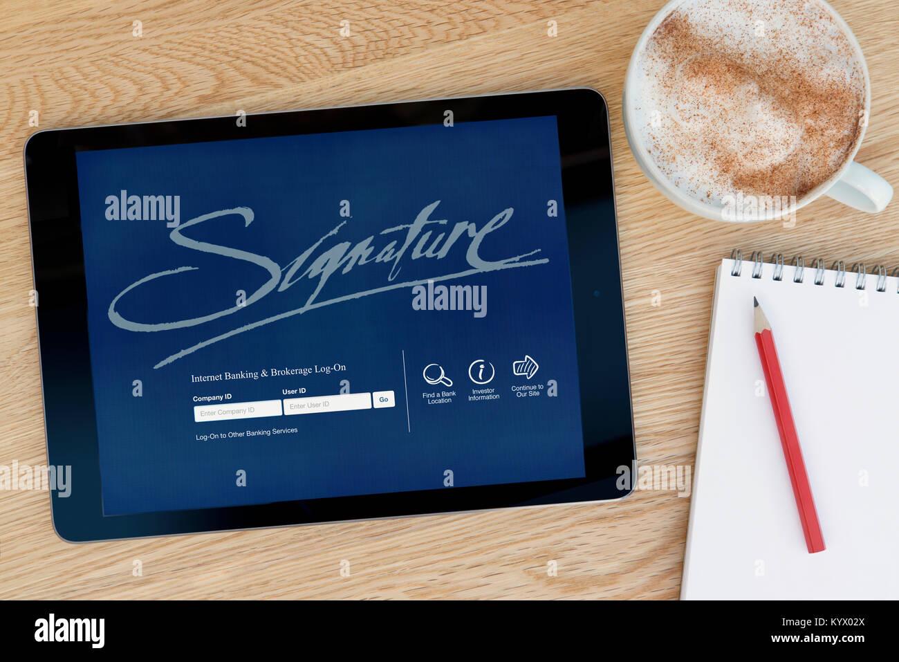 Die Unterschrift Bank Website auf einem iPad Tablet, auf einen hölzernen Tisch neben einem Notizblock, Bleistift Stockbild