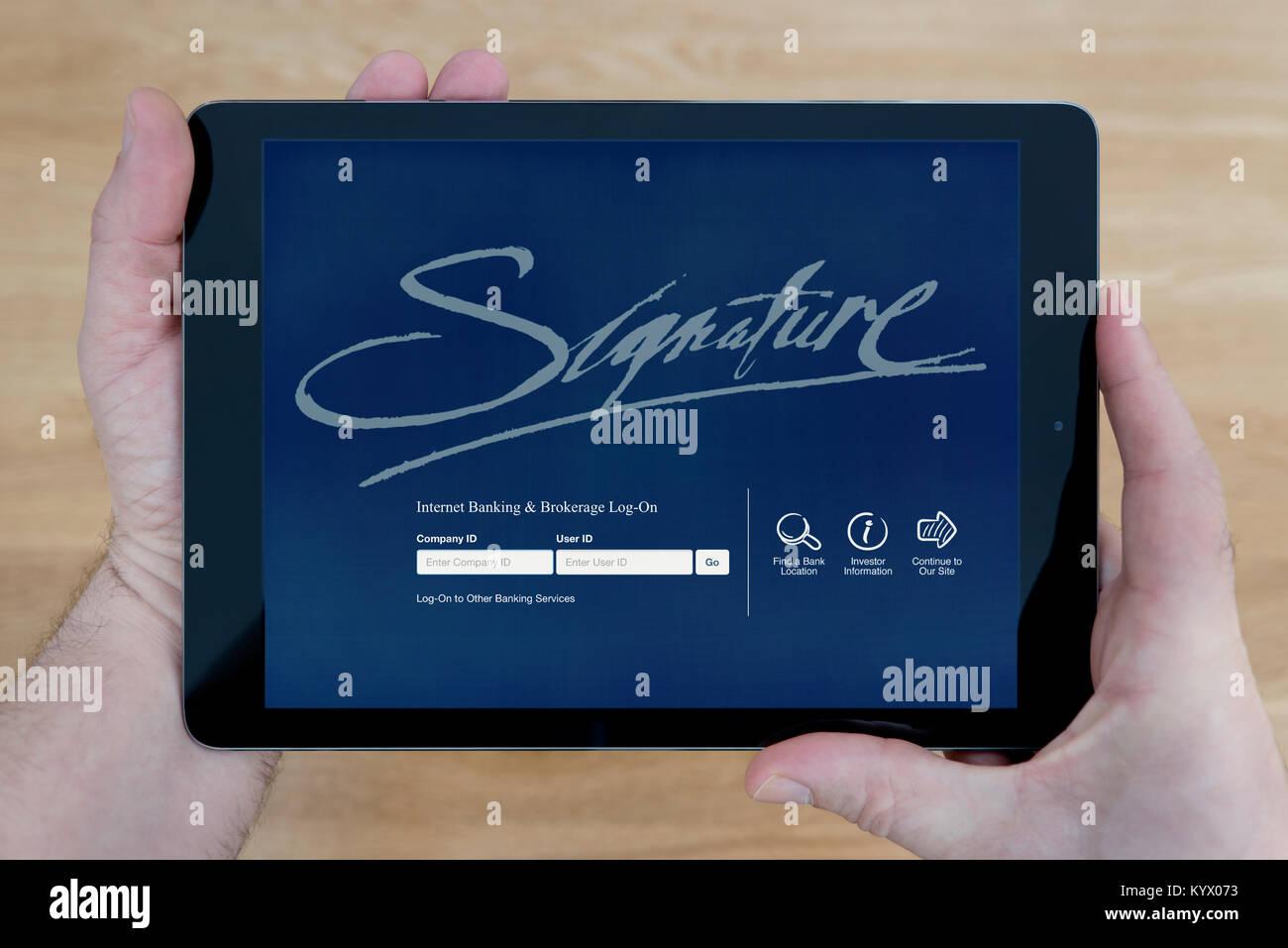 Ein Mann sieht in der Signature Bank Website auf seinem iPad tablet device, mit einem hölzernen Tischplatte Stockbild