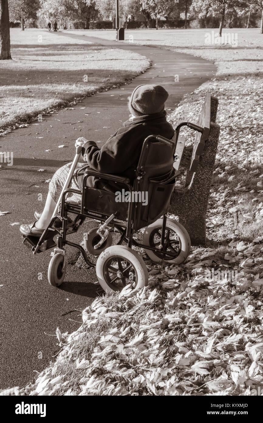 90 Jahre alte Frau im Rollstuhl in den öffentlichen Park. UK: Pflege, Einsamkeit, Mobilität, Alterung Stockbild