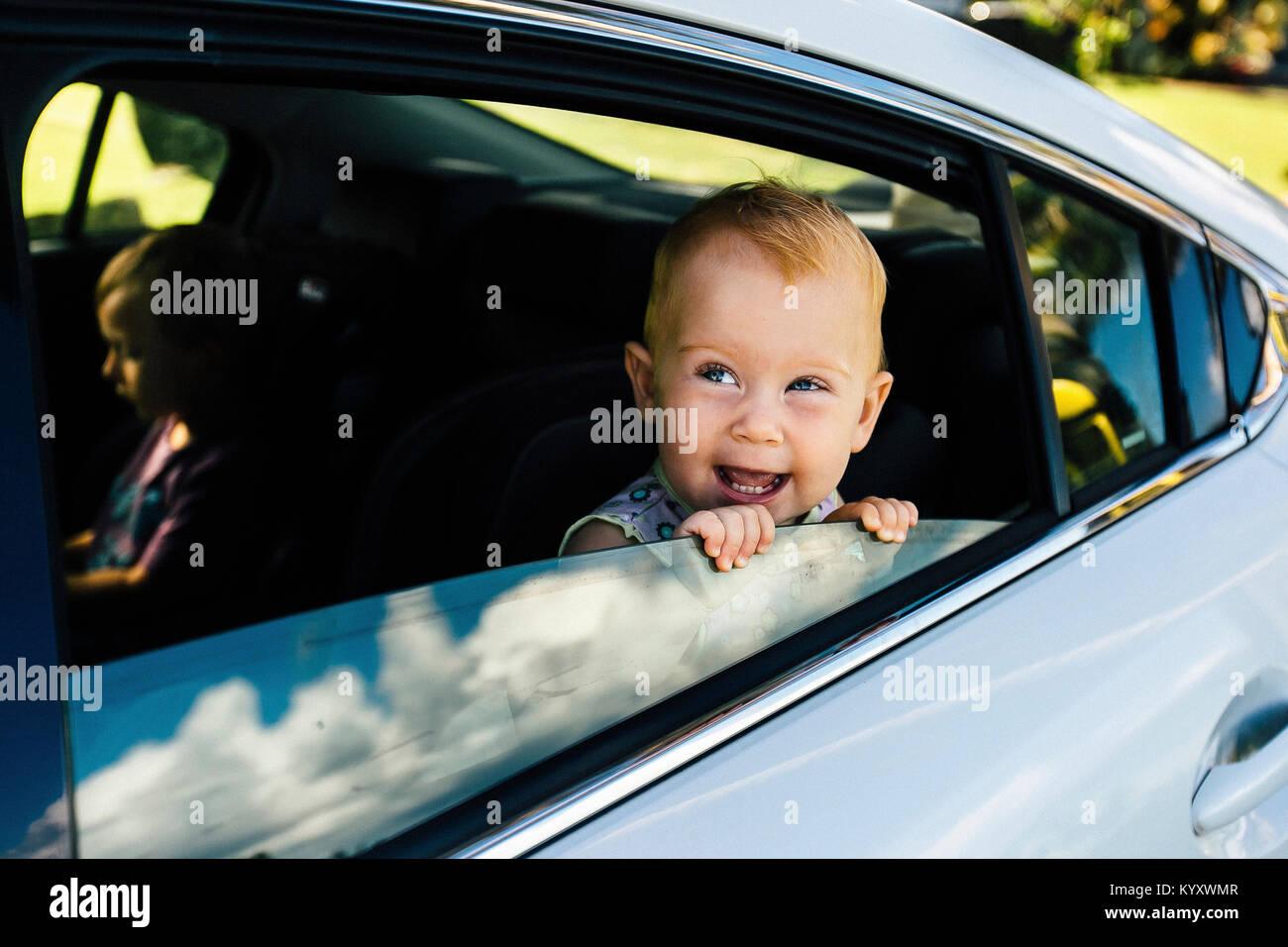 Kinder sitzen auf Auto Stockbild