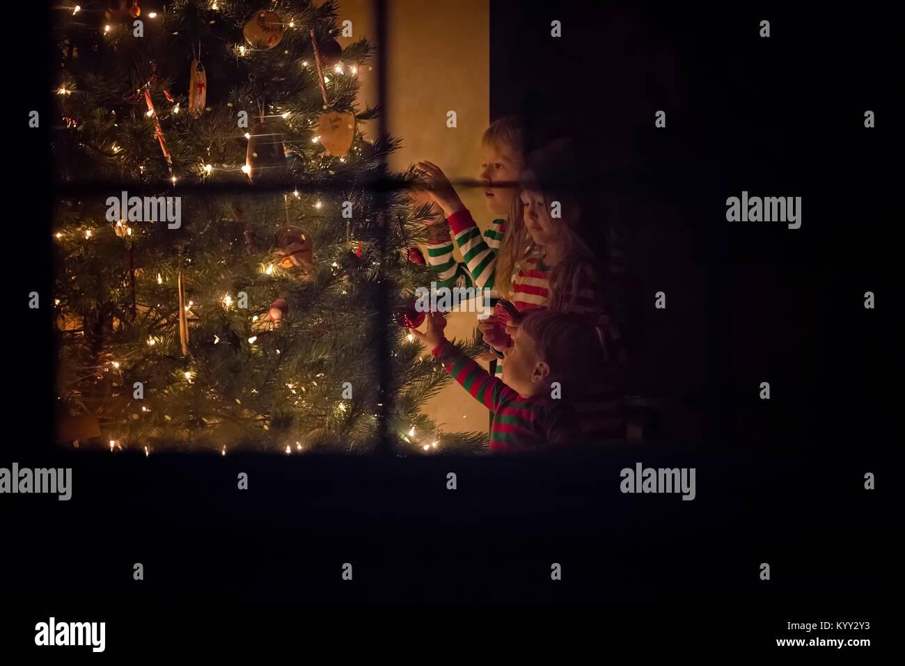 Geschwister schmücken Weihnachtsbaum zu Hause während Weihnachten Stockbild