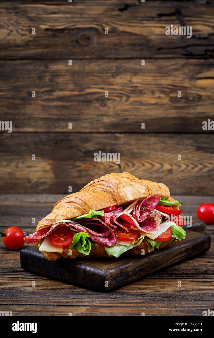 Leckeres Frühstück. Appetitlich Croissant mit Salami und Käse und Tomaten Stockbild