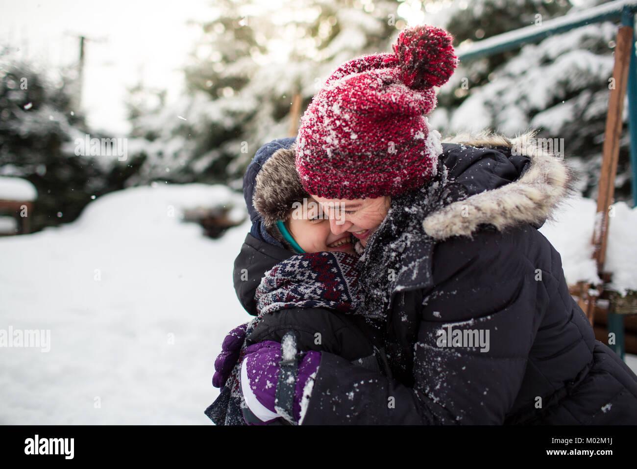 Seitliche Sicht auf eine glückliche Mutter und Sohn umarmen nach einer Schneeballschlacht. Familie Spaß Stockbild