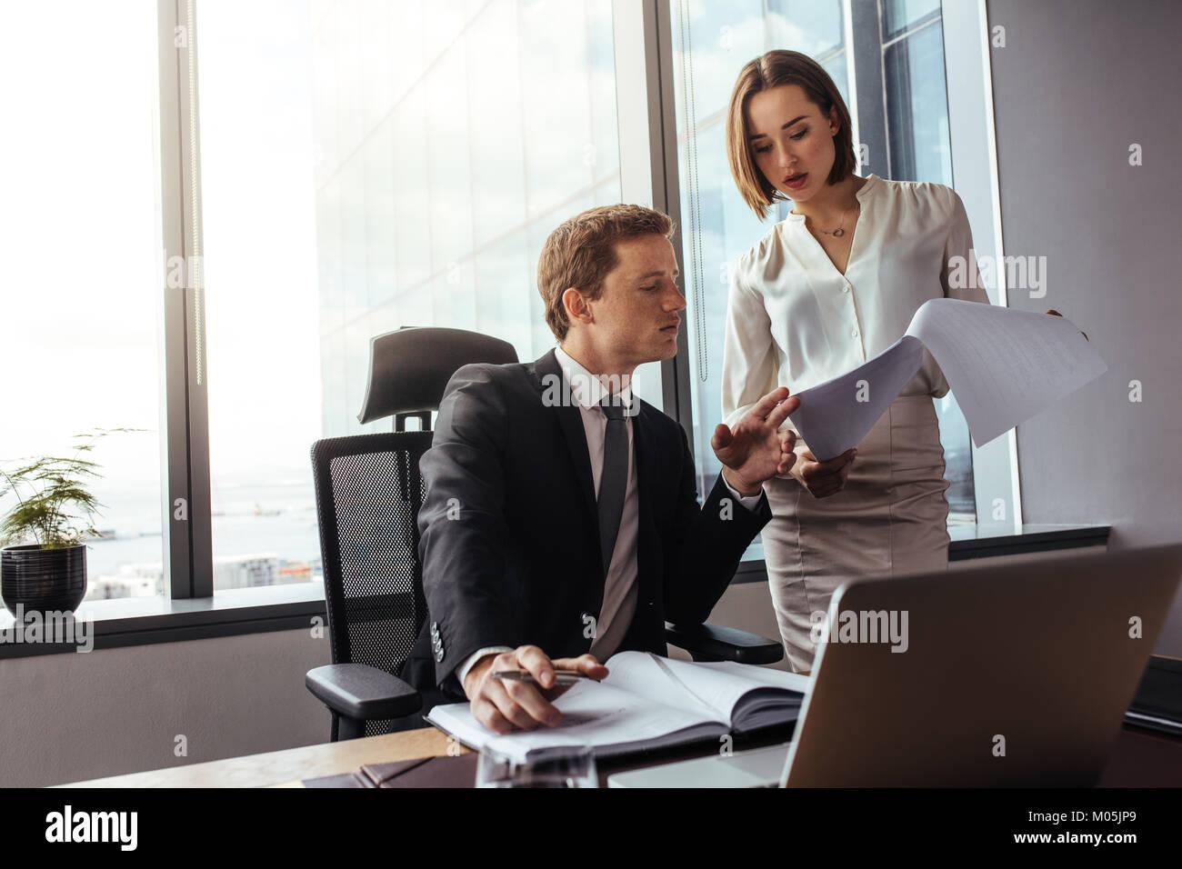 Zwei junge Geschäftsleute, die Ergebnisse zu analysieren und zu diskutieren. Geschäftsmann mit Kollegin Lesen von Stockfoto