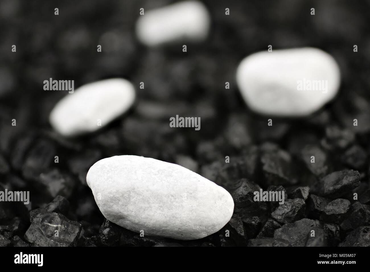 Weißen Kieselsteinen vor schwarzen Hintergrund mit schwarzem Kies Stockbild