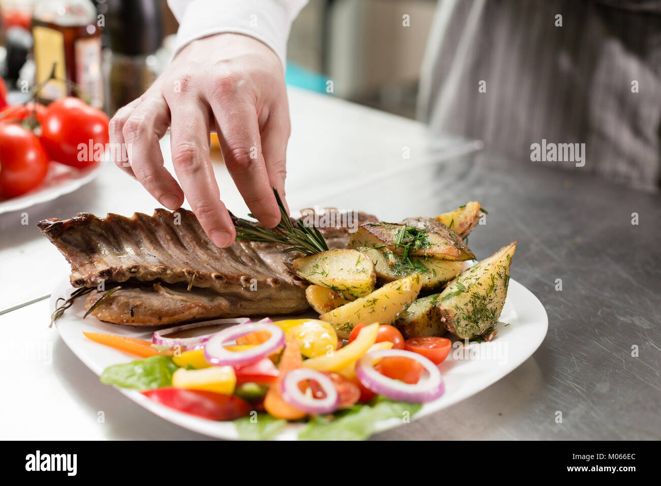 Der Küchenchef im Restaurant. Gegrillter Lammrücken mit Bratkartoffeln und frischem Gemüse. closeup Stockbild